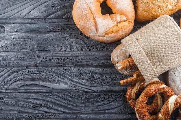 Vue de dessus des produits de boulangerie avec du pain, bagel turc sur une surface en bois gris. espace libre horizontal pour votre texte