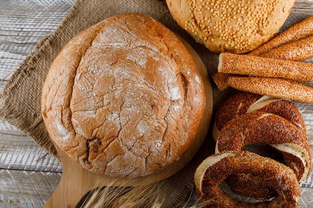 Vue de dessus des produits de boulangerie avec de l'orge sur une planche à découper et une surface en bois. horizontal