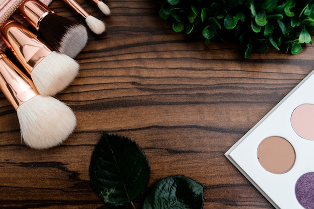 Vue de dessus des produits cosmétiques et de maquillage et accessoires sur fond en bois blanc