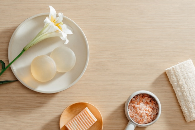Vue de dessus des produits de soins de la peau de spa bio avec du sel, des fleurs, des serviettes et des savons de riz
