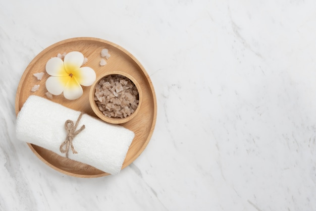 Vue de dessus des produits spa dans un plateau en bois de forme ronde sur marbre blanc.