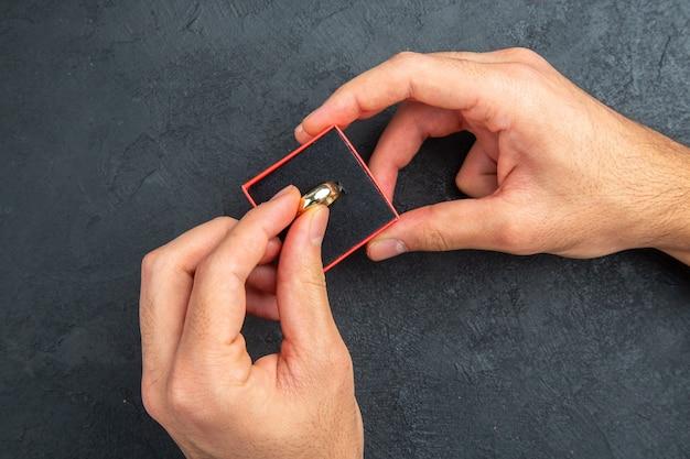 Vue de dessus proposition de mariage concept homme mains tenant l'anneau de mariage