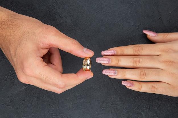 Vue de dessus proposition de mariage concept main de l'homme plaçant l'anneau sur la main de la femme sur fond noir