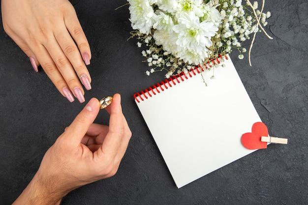 Vue de dessus proposition de mariage concept main masculine plaçant l'anneau sur la main féminine cahier de fleurs sur fond sombre