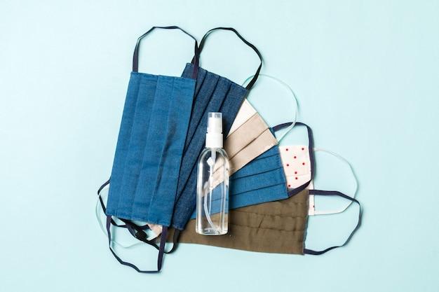 Vue de dessus de la protection individuelle telle qu'une pile de masques textiles faits maison et de désinfectant pour les mains à l'alcool sur fond bleu. concept de soins de santé avec espace copie.