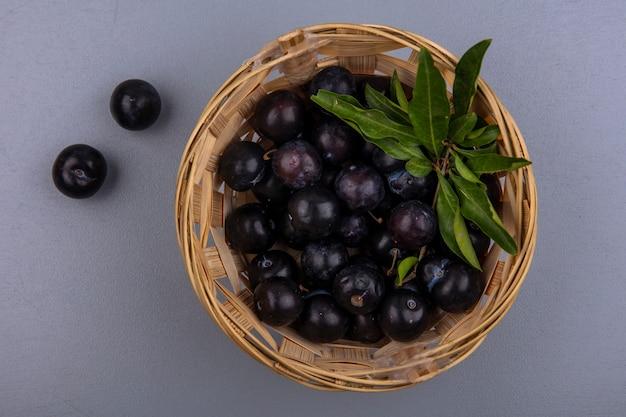 Vue de dessus prune cerise dans un panier sur fond gris