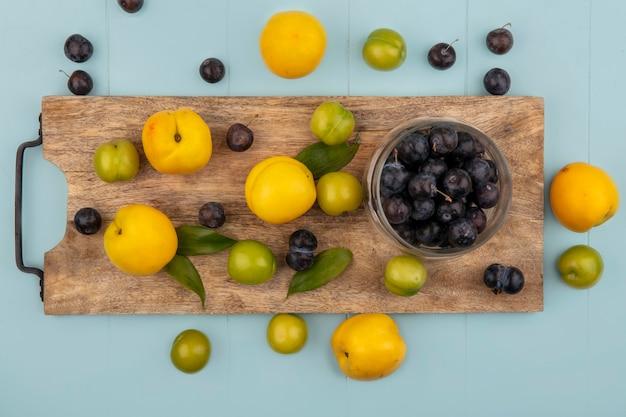 Vue de dessus de prunelles aigre violet foncé sur un bol en verre sur une planche de cuisine en bois avec des pêches jaunes sur fond bleu