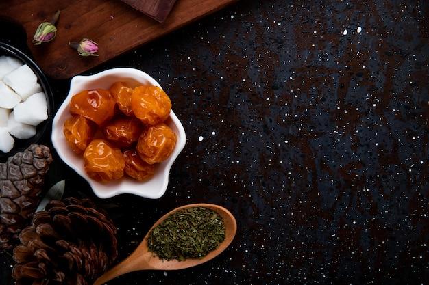 Vue de dessus des prunes cerises séchées dans une soucoupe et une cuillère en bois avec de la menthe poivrée séchée sur fond noir avec copie espace