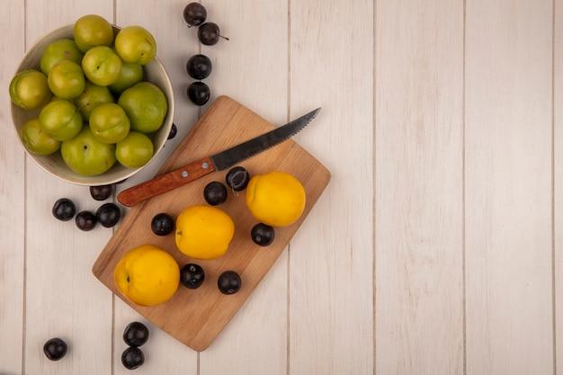 Vue de dessus des prunes cerises vertes sur un bol avec des pêches jaunes sur une planche de cuisine en bois avec un couteau avec des prunes sur un fond en bois gris avec espace copie