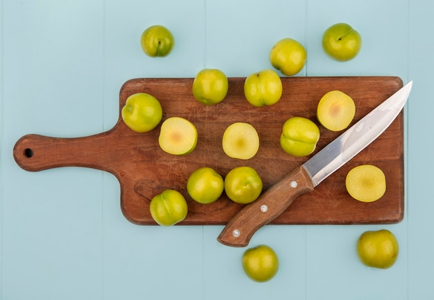 Vue de dessus des prunes cerises vertes fraîches sur une planche de cuisine en bois avec un couteau sur un fond bleu