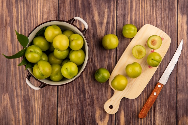 Vue de dessus de prunes coupées entières et à moitié dans un bol et sur une planche à découper avec un couteau sur fond de bois