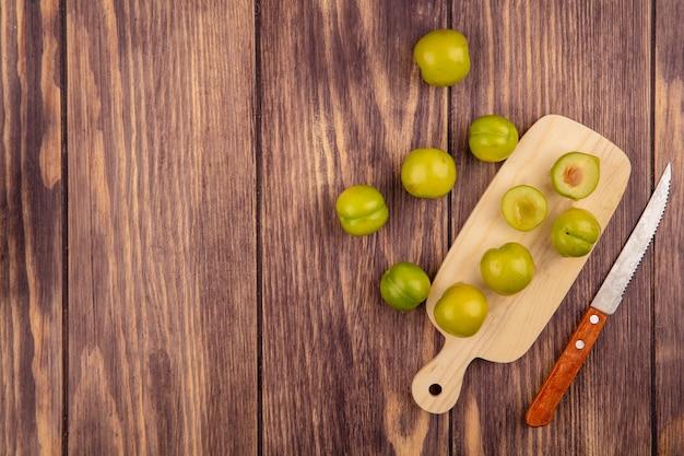 Vue de dessus de prunes coupées entières et à moitié sur une planche à découper avec un couteau sur fond de bois avec espace copie
