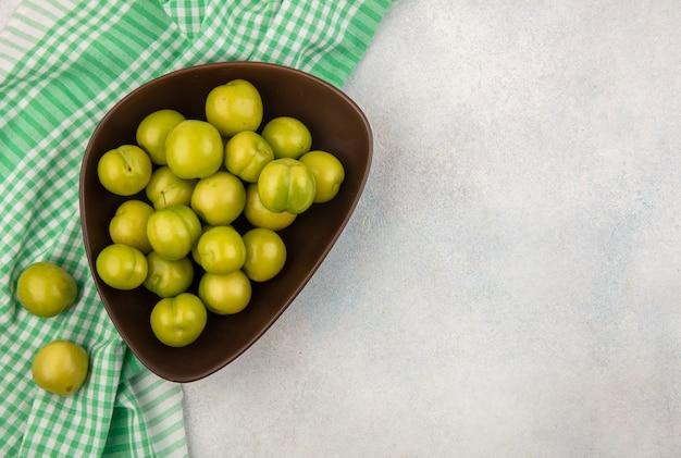 Vue de dessus des prunes dans un bol sur tissu à carreaux sur fond blanc avec copie espace