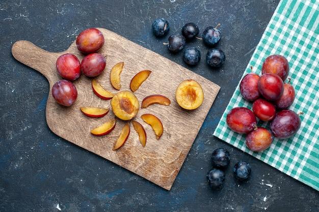 Vue de dessus des prunes fraîches entières moelleuses et juteuses tranchées sur noir, fruits frais d'été de vitamine