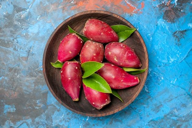 Vue de dessus des prunes mûres fraîches à l'intérieur d'une assiette en bois sur fond bleu