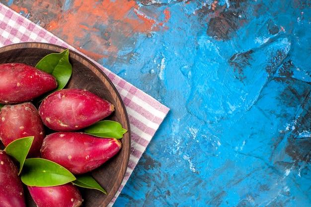 Vue de dessus des prunes mûres fraîches à l'intérieur de la plaque sur fond bleu
