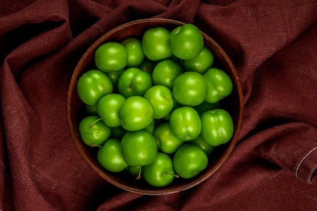 Vue de dessus des prunes vertes dans un bol en bois sur une table en tissu rouge foncé