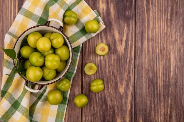 Vue de dessus des prunes vertes dans un bol et sur un tissu à carreaux et sur fond de bois avec espace copie