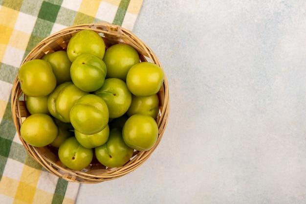Vue de dessus des prunes vertes dans le panier sur tissu à carreaux sur fond blanc avec copie espace