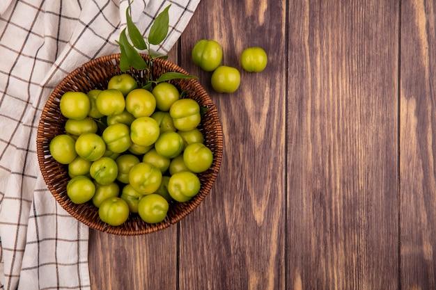 Vue de dessus des prunes vertes dans le panier sur tissu à carreaux et fond en bois avec espace copie