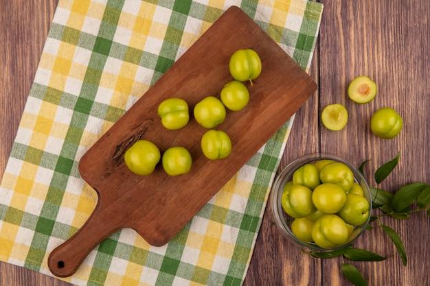 Vue de dessus des prunes vertes sur une planche à découper sur tissu à carreaux et en pot sur fond de bois