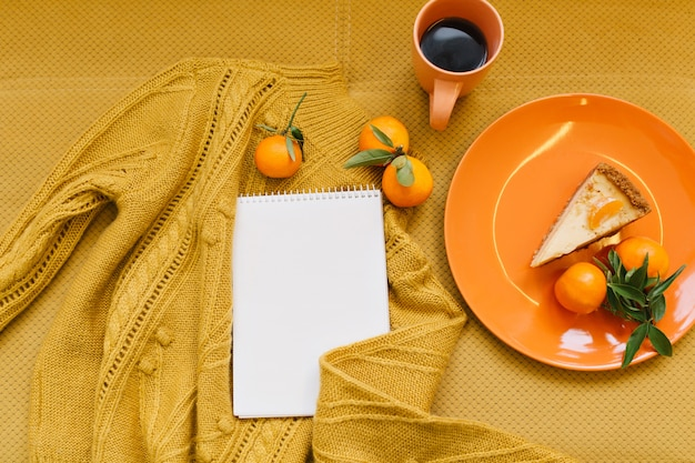 Vue de dessus pull orange tricoté, mandarines, cheesecake, tasse de café, cahier blanc sur table orange