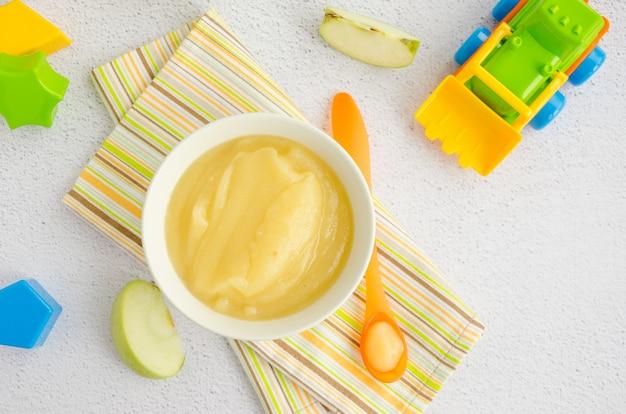 Vue de dessus de la purée de pommes dans un bol avec une cuillère et des jouets