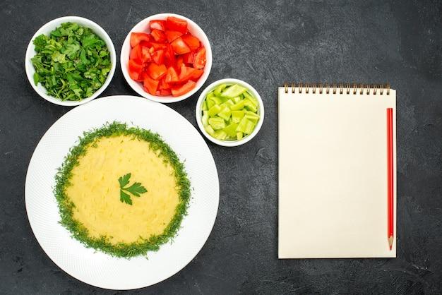 Vue de dessus de purée de pommes de terre avec légumes verts et tomates tranchées sur gris foncé