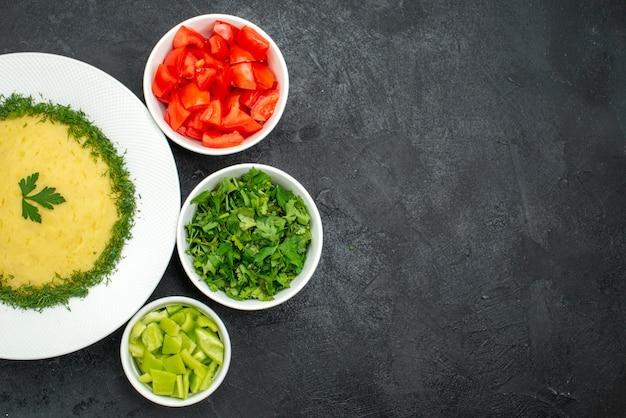 Vue de dessus de purée de pommes de terre avec des légumes verts et des tranches de tomates fraîches sur gris foncé