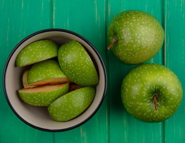 Vue de dessus des quartiers de pomme verte dans un bol avec l'ensemble sur fond vert
