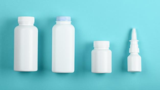 Vue de dessus quatre bouteilles de contenants médicaux blancs sur fond bleu pour maquette et image de marque
