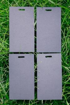 Vue de dessus de quatre étiquettes de prix noires pour la disposition créative des vêtements d'herbe verte avec étiquette pour le logo.