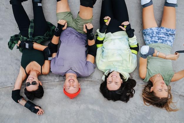 Vue de dessus de quatre patineurs amusants se détendre sur un pavage en béton au skatepark. porter un équipement de protection. les jambes en l'air. vue en grand angle.