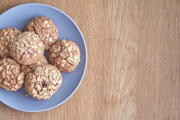 Vue de dessus de quelques biscuits à l'avoine sur une plaque grise sur une surface en bois claire