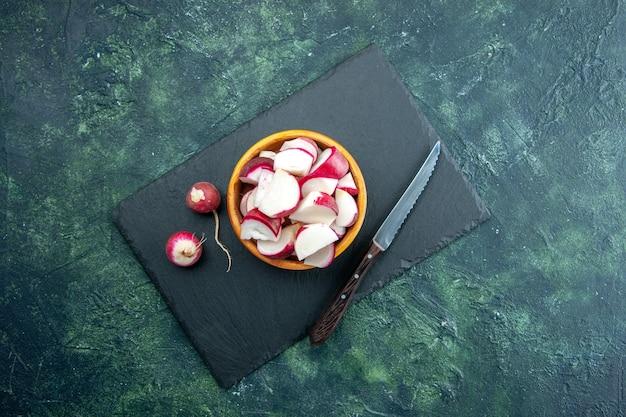 Vue de dessus de radis frais entiers et hachés dans un bol et un couteau sur une planche à découper de couleur foncée sur fond de couleurs mélangées noir vert avec espace libre
