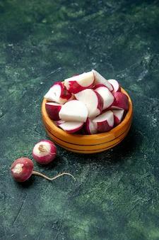 Vue de dessus de radis frais entiers et hachés à l'intérieur et à l'extérieur d'un bol en bois sur fond de couleur sombre avec de l'espace libre