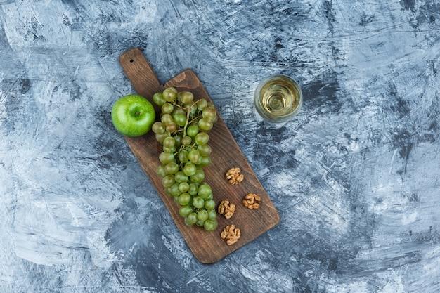 Vue de dessus des raisins blancs, des noix, des pommes sur une planche à découper avec un verre de whisky sur fond de marbre bleu foncé. horizontal