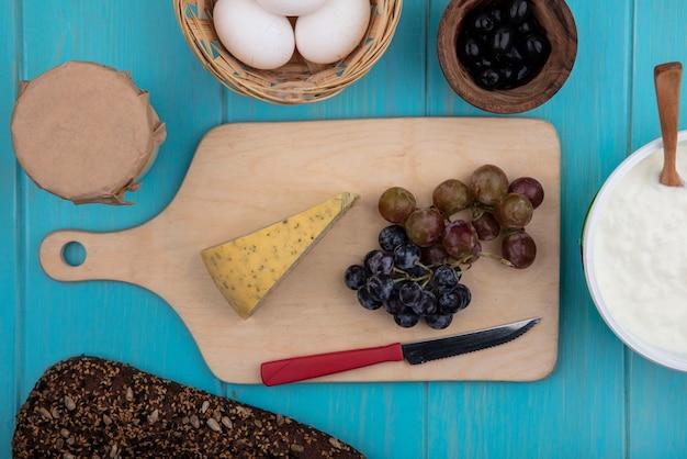 Vue de dessus des raisins avec du fromage sur un stand avec des olives oeufs de poule yaourt et pain noir sur fond turquoise