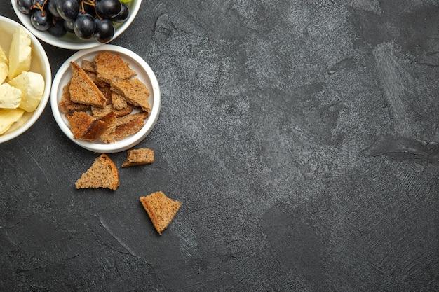 Vue de dessus des raisins frais avec du fromage blanc et du pain noir tranché sur une surface sombre, un plat de petit-déjeuner, des fruits au lait