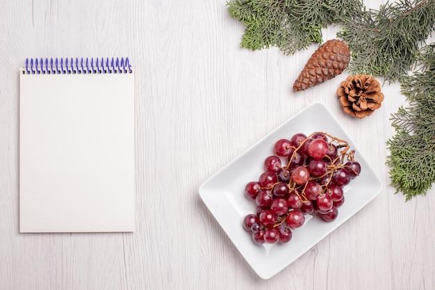 Vue de dessus des raisins frais à l'intérieur de la plaque sur un tableau blanc
