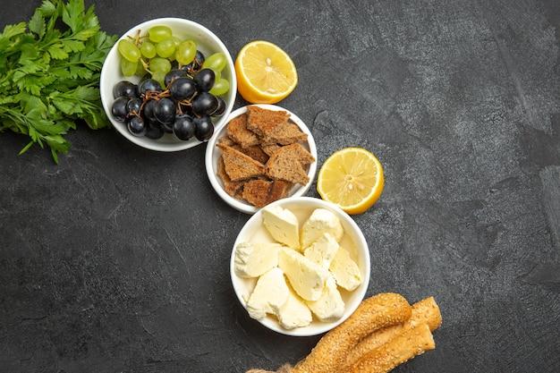 Vue de dessus des raisins frais et moelleux avec du fromage blanc et du pain tranché sur une surface sombre, des fruits au lait