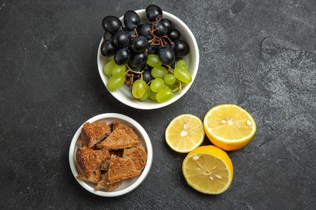 Vue de dessus des raisins frais avec des tranches de citron sur la surface sombre des fruits mûrs et mûrs de la vitamine