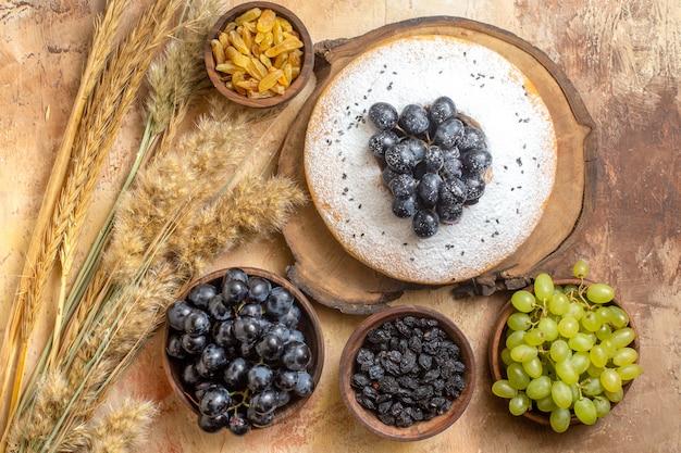 Vue de dessus des raisins un gâteau avec des raisins sur le conseil raisins verts et noirs épillets de raisins