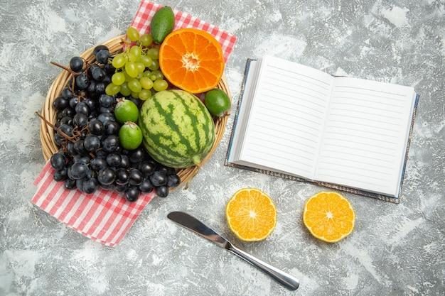 Vue de dessus des raisins noirs frais avec des oranges et du feijoa sur une surface blanche, des fruits mûrs, des vitamines douces, des arbres frais