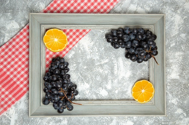 Vue de dessus des raisins noirs frais avec des oranges à l'intérieur du cadre sur une surface blanche fruits mûrs moelleux frais