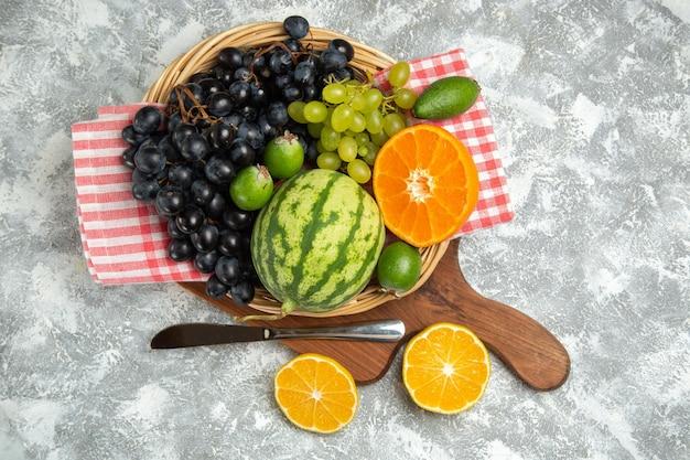 Vue de dessus des raisins noirs frais avec des oranges et de la pastèque sur une surface blanche, des fruits mûrs, des vitamines douces, des arbres frais