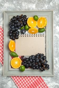 Vue de dessus des raisins noirs frais avec des tranches d'oranges sur des fruits de surface blanche mûrs moelleux frais