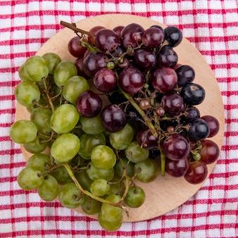 Vue de dessus des raisins sur une planche à découper sur fond de tissu à carreaux