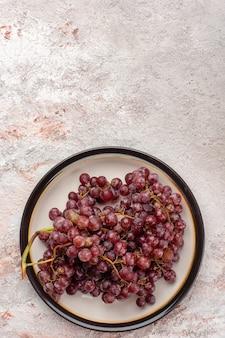 Vue de dessus des raisins rouges frais fruits juteux et moelleux à l'intérieur de la plaque sur la surface blanche