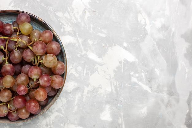 Vue de dessus raisins rouges frais fruits sucrés moelleux juteux sur un bureau blanc